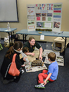 Breanne Musselman (C) shows a red tailed tortoise to Vincent Fernandez (R) and his mom, Patricia Fernandez (L) and his sister Elena Fernandez (2FROM R) during an event in which Delaware Valley College students will host a family friendly Animals in the Public Eye Monday March 23, 2015 at the Doylestown Free Library in Doylestown, Pennsylvania. (Photo by William Thomas Cain/Cain Images)