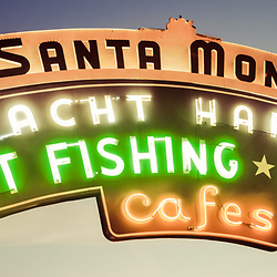 "Santa Monica Pier sign panorama vintage retro picture at dusk.  Panorama picture ratio is 1:3. The famous Santa Monica pier neon sign says ""Santa Monica Yacht Harbor Sport Fishing Boating Cafes"". Santa Monica Pier is a landmark located in Los Angeles County Southern California and has an amusement park with a ferris wheel, roller coaster, restaurants, and other attractions."