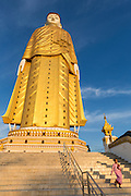 Nun walking down stairs at Maha Bodhi Tahtaung standing Buddha, Monywa