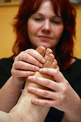 Aromatherapist treating day care service users foot,