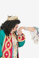 Senior king kissing the hand of queen over gray background