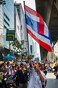 "20 DECEMBER 2013 - BANGKOK, THAILAND:  An anti-government protestor carries a Thai flag down Silom Road in Bangkok. Thousands of anti-government protestors, supporters of the so called Peoples Democratic Reform Committee (PRDC), jammed the Silom area, the ""Wall Street"" of Bangkok, Friday as a part of the ongoing protests against the caretaker government of Yingluck Shinawatra. Yingluck dissolved the Thai Parliament earlier this month and called for national elections on Feb. 2, 2014. The protestors want the elections postponed and the caretaker government to step down. The Thai election commission ruled Friday that the election would go on dispite the protests.         PHOTO BY JACK KURTZ"