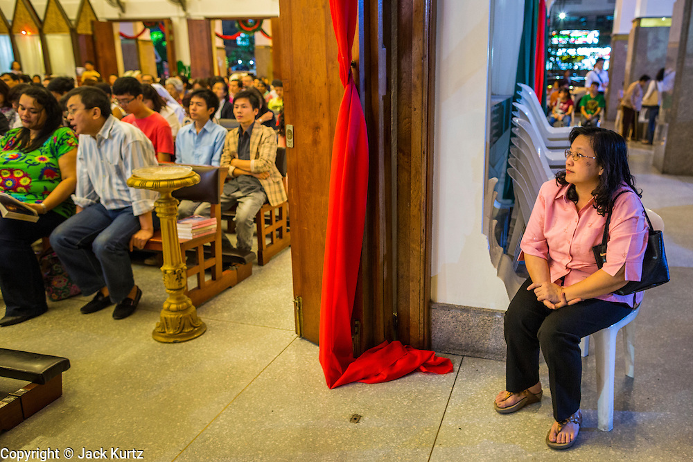 24 DECEMBER 2013 - BANGKOK, THAILAND: A woman sits in the breezeway outside the church during Christmas services at Holy Redeemer Church in Bangkok. Thailand is predominantly Buddhist but Christmas is widely celebrated throughout the country. Buddhists mark the day with secular gift giving but there are about 300,000 Catholics in Thailand who celebrate religious Christmas. Catholics first came to Thailand (then Siam) in 1567 as chaplain for Portuguese mercenaries in the employ of the Siamese monarchy. There has been a continuous Catholic presence in Thailand since then.   PHOTO BY JACK KURTZ