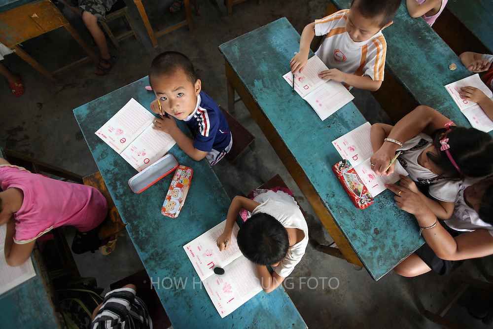 epa02877954 Kindergarten students practice writing during a class in Dongba Experimental School, a school for children of migrant workers on the outskirts of Beijing, where the school term has started early as a forced closure looms in China on 23 August 2011. The Dongba Experimental School is one of more than 20 schools for children of migrant workers that were deemed 'unsafe' that has been ordered to shut down by the authorities in Beijing, forcing thousands of students to scramble for alternative schools. The school, which has been operating for the past 11 years, started its new term two weeks earlier than usual in a bid to prevent the school from being demolished. Yang Qin, the school's principal, said local officials have even gone as far as to stop their water and electricity supply, forcing the school to rent a generator and and transport water using a water cart from parents' homes in the neighbourhood. Embittered parents cite long distances and the lack of transport for alternative schools and many even face the grim prospect of separating from their children and sending them back to schools in their hometowns in other provinces. Some have taken on a wait and see attitude hoping the school will not be closed down while others have asked the school to refund school fees of 800 RMB (86euros) for the term. Migrant workers in Chinese cities are generally poorly educated and are subjected to various difficulties of low pay, inadequate social security, and discrimination, mainly due to a hereditary household registration or 'hukou' system that divides the population into urban and rural residents and limits migrants access to urban services like state education.  EPA/HOW HWEE YOUNG
