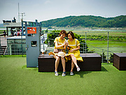 09 JUNE 2018 - IMJINGAK, PAJU, SOUTH KOREA:  Women sitting on a lookout on the South Korean side of the Korean DMZ in Imjingak look at a smart phone. The Imjin River and North Korea are behind them. Imjingak is a park and greenspace in South Korea that is farthest north most people can go without military authorization. The park is on the south bank of Imjin River, which separates South Korea from North Korea and is close the industrial park in Kaesong, North Korea that South and North Korea have jointly operated.    PHOTO BY JACK KURTZ