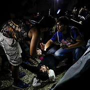 A refugee is resuscitated after experiencing a seizure from tear gas fired by Greek police during clashes with refugees hours after a fire inside of Moria camp. At least one person was killed by a fire as many refugees and migrants remain trapped in squalid living conditions at the camp on Lesvos Island in Greece on Sunday, September 29, 2019. Credit: Byron Smith