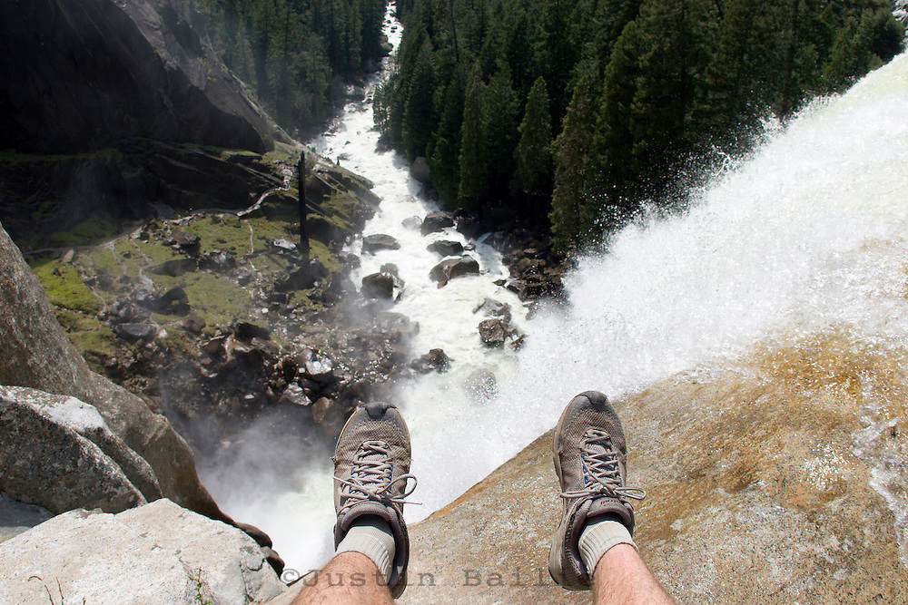 Young man sitting on edge near waterfall in Yosemite National Park, CA