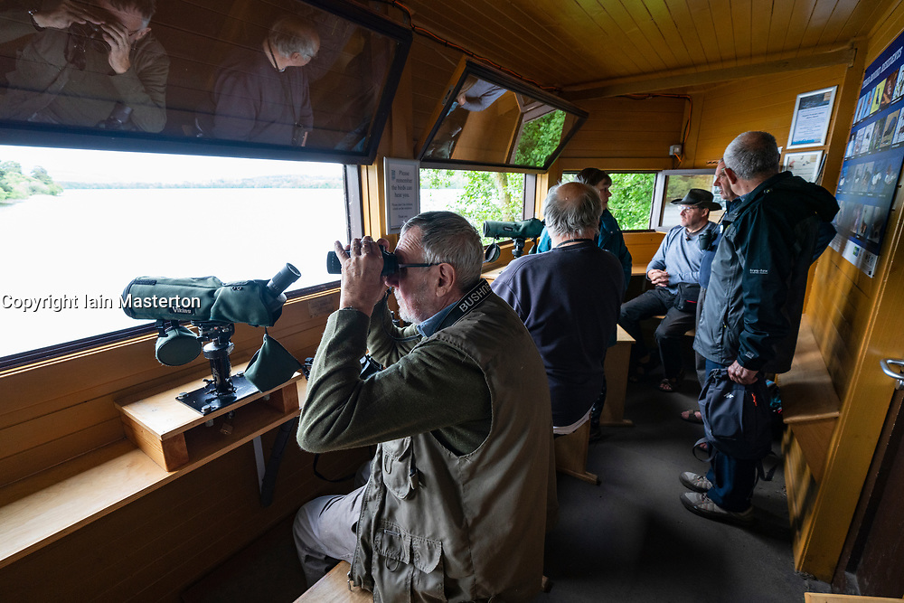 Birdwatchers inside Osprey birdwatching hide at Scottish Wildlife Trust visitor centre at Loch of the Lowes, new Dunkeld in Perthshire, Scotland, UK
