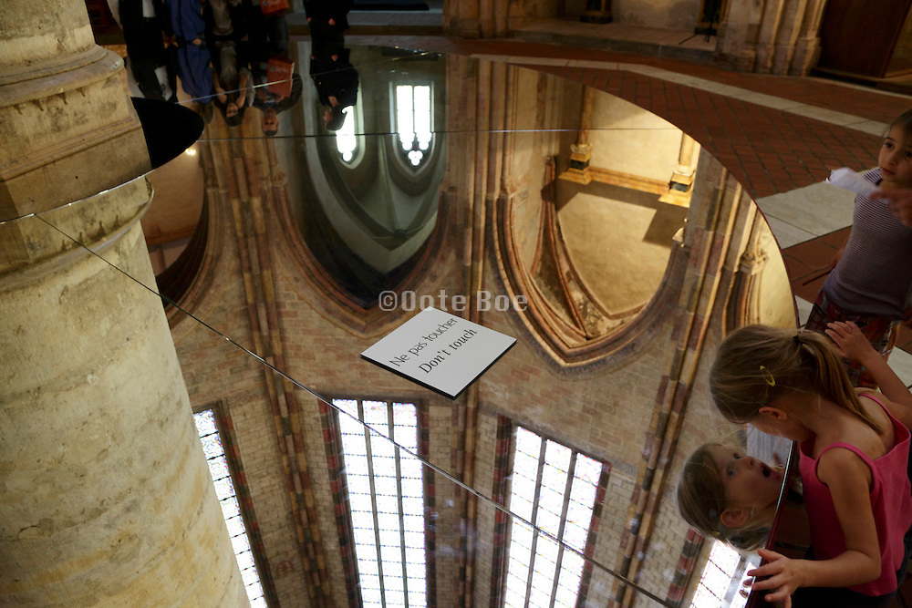 child looking with surprise in a mirror to see the vaulted space of the church Les Jacobins Toulouse