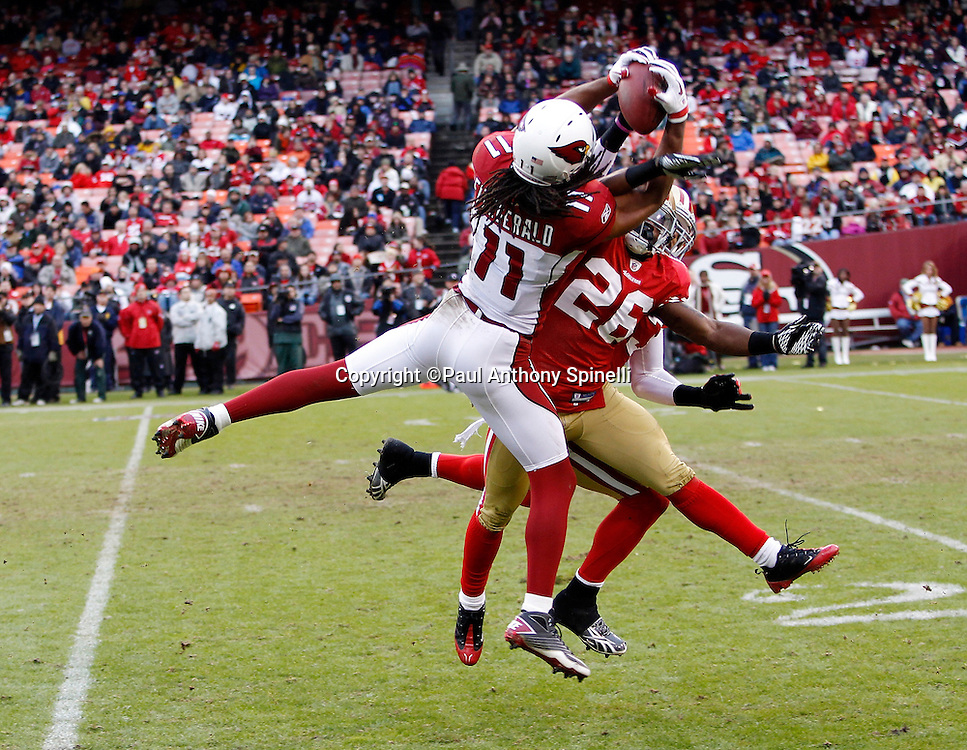 Arizona Cardinals wide receiver Larry Fitzgerald (11) leaps and catches a second quarter pass good for 30 yards and a first down while covered by San Francisco 49ers cornerback Tramaine Brock (26) and San Francisco 49ers safety Taylor Mays (23) during the NFL week 17 football game on Sunday, January 2, 2011 in San Francisco, California. The 49ers won the game 38-7. (©Paul Anthony Spinelli)