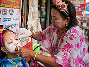 "17 FEBRUARY 2015 - BANGKOK, THAILAND: A woman works on a client at a threading stand on Charoen Krung Road in Bangkok's Chinatown. About a dozen people, mostly women, have set up shop on the sidewalk to do hair removal for clients. They use thread to remove hair, a practice called ""threading"" which originated in India more than 6,000 years ago. It's growing in popularity in the US and Europe as an alternative to waxing. A cotton or polyester thread is pulled along unwanted hair in a twisting motion, the hair is trapped in a mini lasso, and lifted out of the follicle.    PHOTO BY JACK KURTZ"