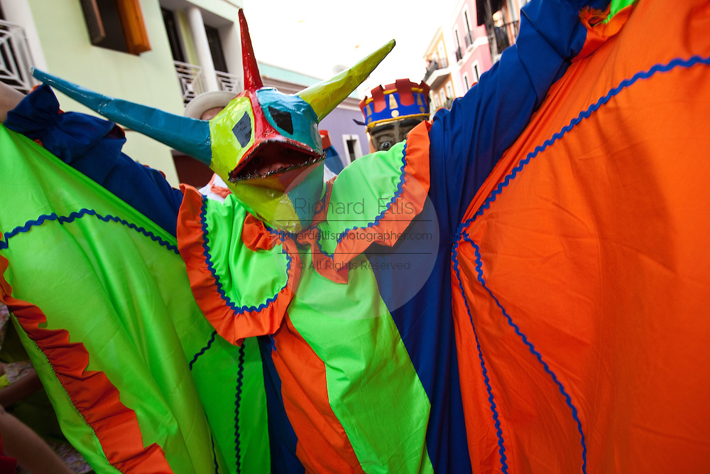 Costumed revelers parade through the streets of Old San Juan during the Festival of San Sebastian in San Juan, Puerto Rico.