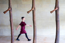 "© Licensed to London News Pictures. 24/05/2018. Wakefield UK. A visitor walks past a sculpture by Giuseppe Penone made of Bronze & called ""Trattenere 6,8,12 anni di crescita"" at the Yorkshire Sculpture park this morning. Giuseppe Penone presents his extensive new exhibition in YSP's light-filled Underground Gallery and across the historic landscape. Works drawn from the past five decades of Penone's career, including many never shown in the UK, trace his evolving and thoughtful consideration of humanity's intimate relationship with the natural world. His poetic practice addresses themes around the body, nature, time, touch and memory, played out across different materials from stone, acacia thorns and graphite, to thousands of laurel leaves. Photo credit: Andrew McCaren/LNP"