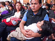 07 FEBRUARY 2011 - PHOENIX, AZ:  MARCO GARDUNO, an immigrant, holds his son, DYLAN GARDUNO, a US citizen by birth, during a senate committee meeting on restricting birthright citizenship at the Arizona Capitol Monday, February 7. The Arizona State Legislature, led by the State Senate is debating the 14th Amendment, which would bar US citizenship for children born in the US to undocumented immigrants. The bill has broad support among Republicans, who are the majority party, in the state legislature but not among Democrats. The law is also very unpopular in the state's Latino and immigrant communities.     Photo by Jack Kurtz