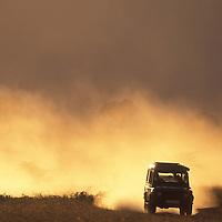 Africa, Kenya, Masai Mara Game Reserve, Setting sun lights cloud of dust from safari truck driving across savanna
