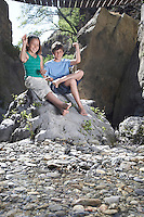 Boy and girl (10-12) sitting on rock throwing stones