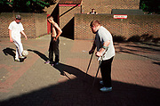 Teenage boys playing football outside in a housing estate one on crutches Lambeth Walk South London c.2000