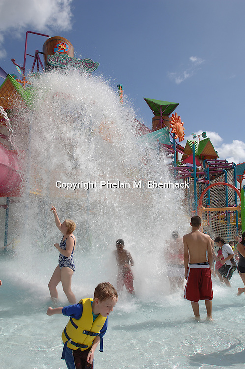 Park guests are doused with a deluge of water at the Walkabout Waters area at Sea World's new waterpark Aquatica in Orlando, Florida.