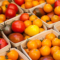 Baskets of yellow, red heirloom cherry and pear tomatoes at a farmers market.