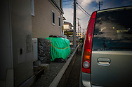 Soil irradiated by fallout from Fukushima Daiichi during its meltdown five years ago, removed to a depth of between 2cm and 5cm (0.8 - 2 inches) during decontamination and discretely stored in green sheeting between a house and parked cars.  Fukushima, Japan.  Space is always limited in Japan, as is privacy.  So, families in Fukushima have been creative in how they store the soil until a permanent dumpsite can be found.