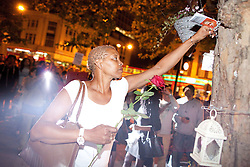 © Licensed to London News Pictures . 21/08/2012 . London , UK . A woman places a rose by a tree outside Brixton Police Station . Protesters march from Lambeth Town Hall to Brixton police station to demonstrate against deaths in police custody . Relatives of Sean Rigg , who died in police custody in August 2008 , lead the march . Video has emerged of a man being detained in Brixton on Sunday ( 19th August ) during which it is alleged police officers stamped on his head . Protesters delivered a formal complaint about the incident to the counter of Brixton Police Station , following the march . Photo credit : Joel Goodman/LNP