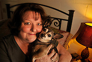 A chronically ill senior patient holds her pet dog.