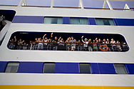 Students wave to disembarking passengers on board a cruise ship in Ft. Lauderdale, Florida after circumnavigating the globe onboard the ship.