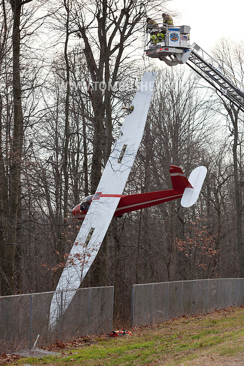 Town of Wallkill, New York - Mechanicstown firefighters work stabilize a glider that crashed into trees at Randall Airport before removing the pilot on Dec. 2, 2012.