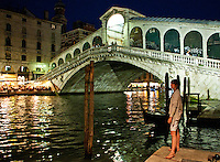 A figure is dreaming at the Rialto Bridge and the Grand Canal at night. The reflection of the lights on the water, the well lit canal side restaurants and the architecture all lend this wonderful scene a beautiful atmosphere.