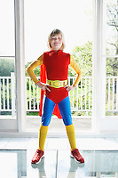 Portrait of young boy (7-9) posing in superhero costume with hands on hip