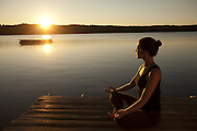 A woman meditating lakeside at sunrise.