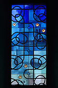 Stained glass window in blue glass with interlacing patterns in lead reminiscent of the Neo-Romanesque period of the 19th century, made by Ateliers Loire, Chartres, in the Upper Chapel, themed as 'L'Engagement' or Commitment, in Le Tresor de la Cathedral d'Angouleme, in Angouleme Cathedral, or the Cathedrale Saint-Pierre d'Angouleme, Angouleme, Charente, France. The 12th century Romanesque cathedral was largely reworked by Paul Abadie in 1852-75. In 2008, Jean-Michel Othoniel was commissioned by DRAC Aquitaine - Limousin - Poitou-Charentes to display the Treasure of the Cathedral in some of its rooms, which opened to the public on 30th September 2016. Picture by Manuel Cohen. L'autorisation de reproduire cette oeuvre doit etre demandee aupres de l'ADAGP/Permission to reproduce this work of art must be obtained from DACS.