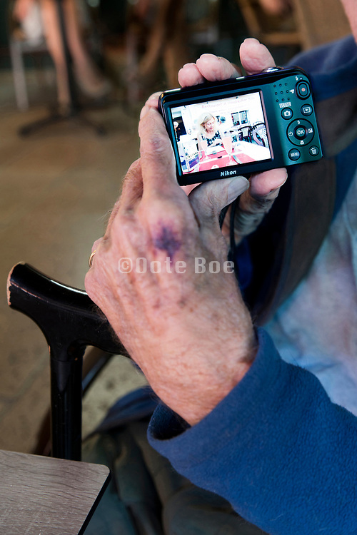 senior man showing picture on his compact camera