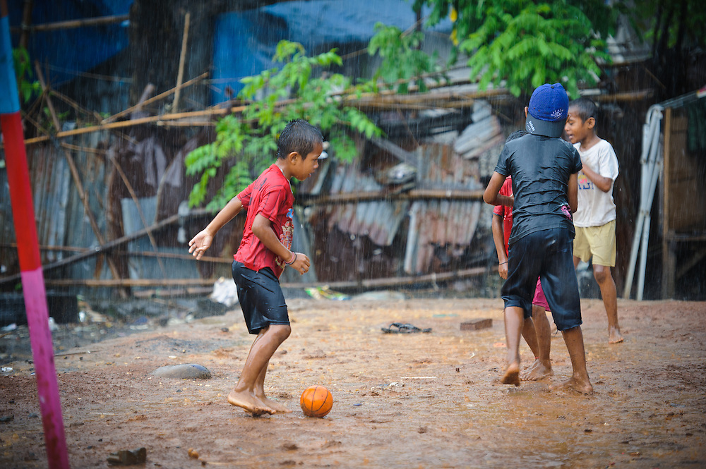 Children playing in the rain outside the school supported by the Sacred Childhoods Foundation, Makassar, Sulawesi, Indonesia.