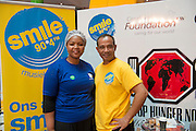 Chairperson Nobuzwe Mbuyiso and Radio 90.4 DJ at the Stop Hunger Now packaging event taking place at Century City, Cape Town on Mandela Day.