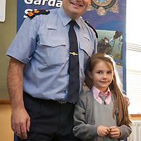 Tori Deasy from Holy Family NS, a medal winner in the recent Ennis Garda Síochána Crime Prevention Art Competition receiving her medal from Superintendant Derek Smart