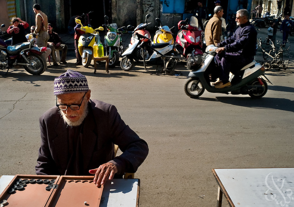An Iraqi man plays backgammon near a scooter sales lot in the scooter and motorcycle market in central Baghdad December 12, 2007. Scooters and motorcycles have become increasingly popular with Iraqis, who see them as a way to combat higher fuel prices and increasing traffic congestion across the capital.