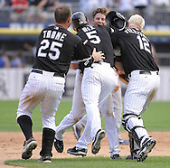 CHICAGO - JUNE 27: Jim Thome #25, Jason Nix #5 and A.J. Pierzynski #12 mob Gordon Beckham #15 of the Chicago White Sox after Beckham won the game with a game winning RBI single in the bottom of the ninth inning against the Chicago Cubs on June 27, 2009 at U.S. Cellular Field in Chicago, Illinois.  The White Sox defeated the Cubs 8-7.  (Photo by Ron Vesely)