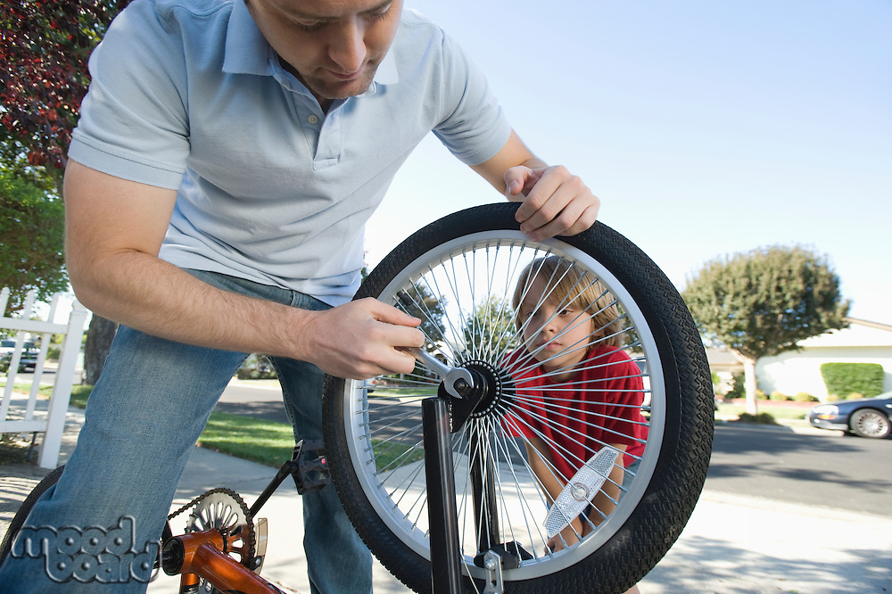 Father fixing son's bicycle tyre