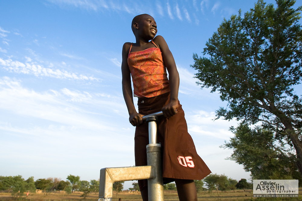 A girl uses a hand pump to get water.