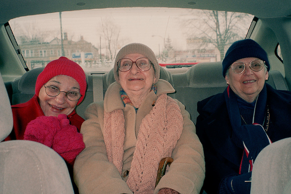 Three mature women seated in back seat of automobile, winter, laughing.