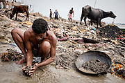 An untouchable is digging for gold nose rings and other valuable jewelry at the burning site of dead bodies, in Varanasi, India.