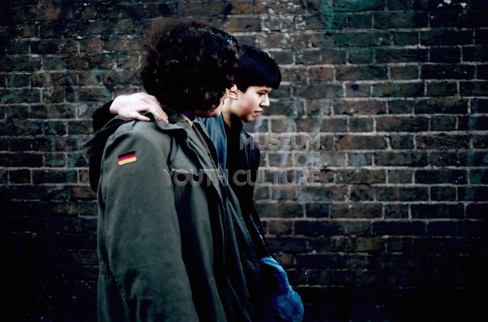 Two Mooody teenage boys walking arm in arm through Camden Town, London UK 2001