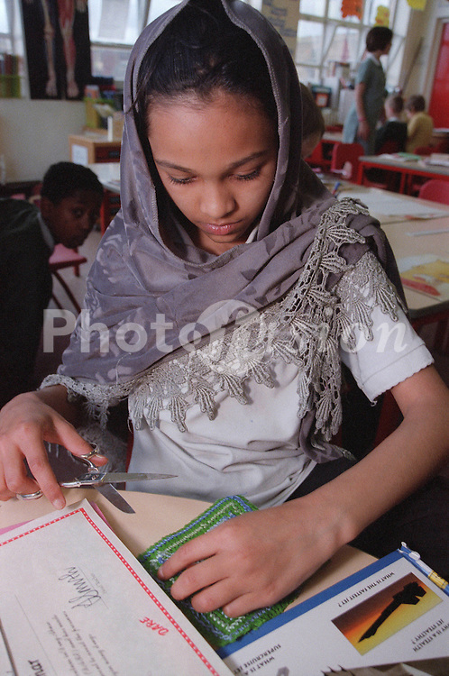 Primary school girl with hair covered by silk scarf using scissors during art and craft lesson,