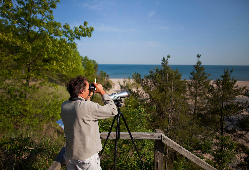 Brendan Grube watches for flocks of migratory birds at Indiana Dunes State Park. Chesterton, Indiana. Grube counts the birds at the park each morning during migration to keep records of the numbers of birds that make the way through the area. Birds migrating north see lake Michigan and often turn around and make their way along the shore instead of attempting the crossing.