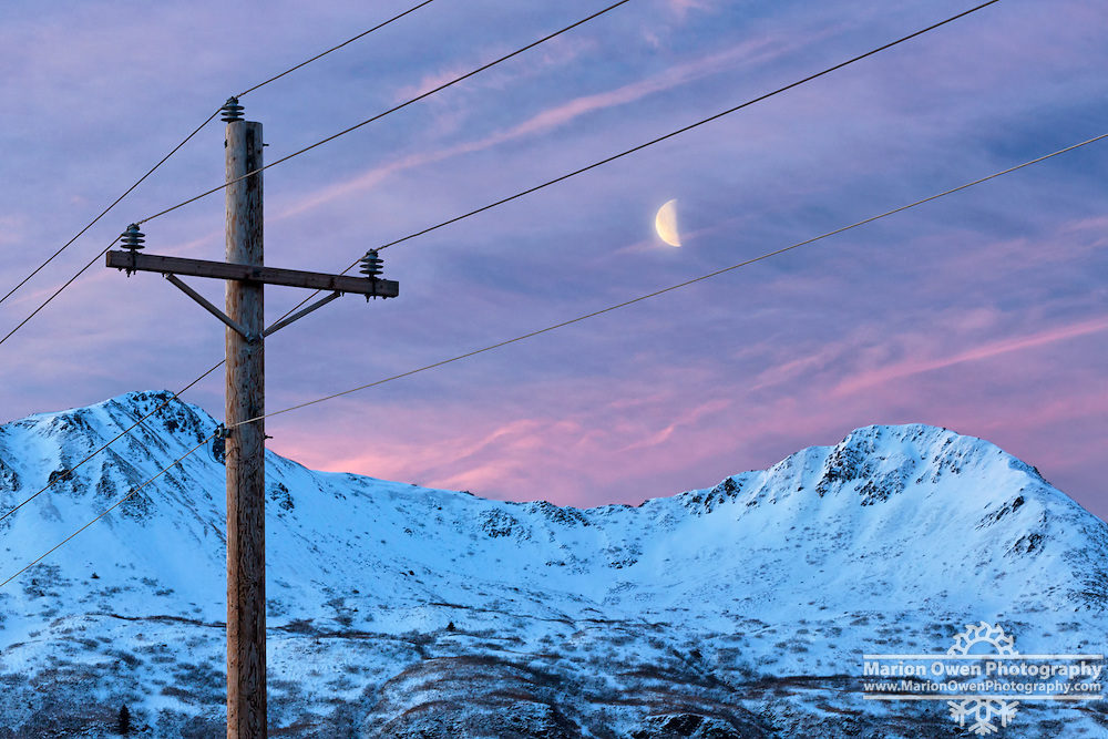 Gibbous moon sets between power lines over snow-capped mountains in Kodiak, Alaska
