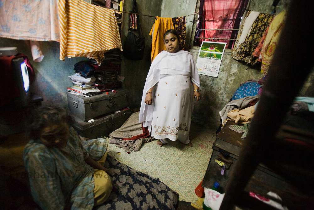 "Abida Sayyed 40 years old, looks on in her kitchen in the Razzaq chawl at the Behrampada area, in Mumbai, India, on Tuesday February 11, 2009. 40 years old. She is a short lady with an iron will, her husband left her with Talaq on the premise that she was short in stature. She had had two children with him. She was introduced to the Mandal when she got her caalways faltering, but after coming into the Mandal her confidence has soared. Her husband has only given her ""Jubani Talaq"" (divorce by word). She says proudly "" I even slapped him once in front of the inspector. Now they all support me."" Being a single women in the settlement area is tough. Her night duties and meeting with mandal ladies are generally misinterpretted. Her motto in her life is to educate her 19 year old daughter. Even her son had quit studying a while ago to support the home. She lives with her ailing mother. Her husband and his family have never contacted her or supported her since. Talking to males around is still a taboo for a single woman in her locality.se here. She had a 5 month old baby girl in her arms when she underwent Talaq proceedings. She never looked back since then. Taking life into hr own hands, Abida trained herself as a domestic help first, and then slowly got trained in nursing and now does private nurse services through the Holy Family Navjit community health center. She said she was very under confident of life before, her health was affected, today she can hold out on her own and challenge society. ."