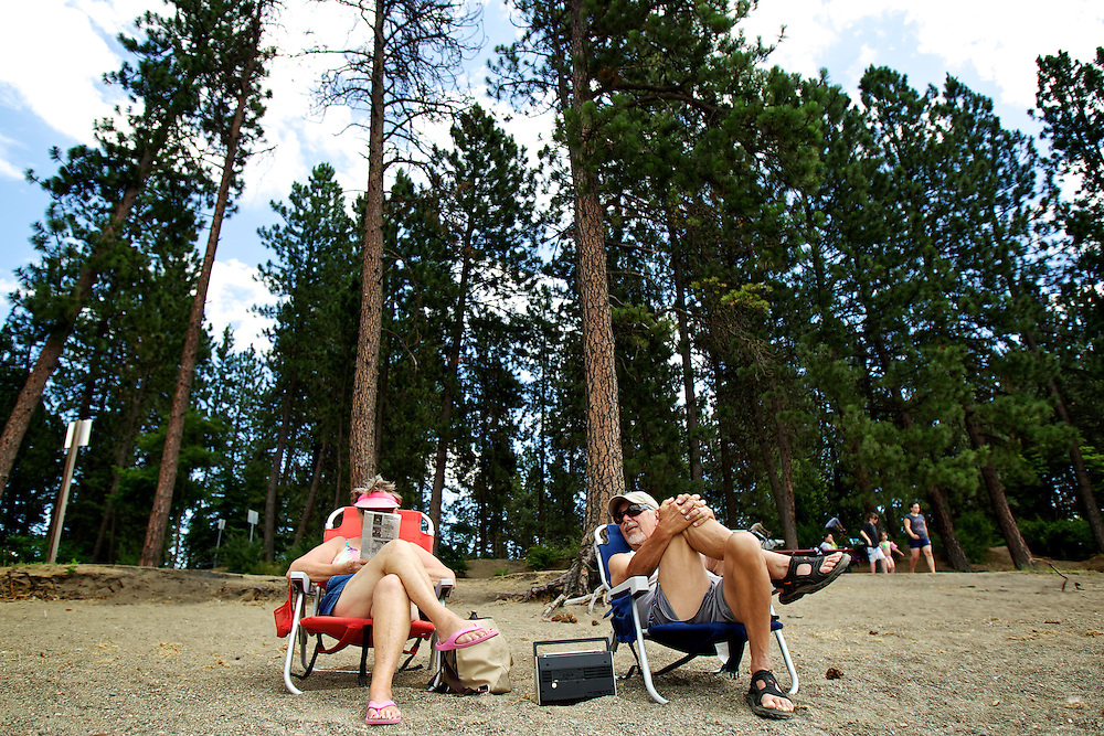 Mary Anne Markowski, left, and her husband Mark Markowski enjoy an outing to the beach at the mouth of the Spokane River with the trees lining Rosenberry Drive behind them Monday.