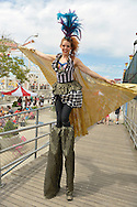 Brooklyn, New York, USA. 10th August 2013. Stilt walker KAE BURKE, of Lady Circus, wears a fancy dress and cape costume, as she walks high on stilts on the wood ramp leading to the famous boardwalk during the 3rd Annual Coney Island History Day celebration.