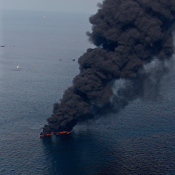 Oil is seen on the surface of the water as smoke billows from controlled oil burns near the site of the BP Plc Deep Water Horizon oil spill site in the Gulf of Mexico off the coast of Louisiana, U.S., on Saturday, June 19, 2010. (Mandatory Credit: Derick E. Hingle)
